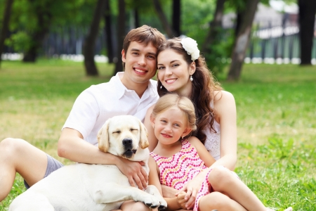 Young Family Outdoors in summer park with a dog photo