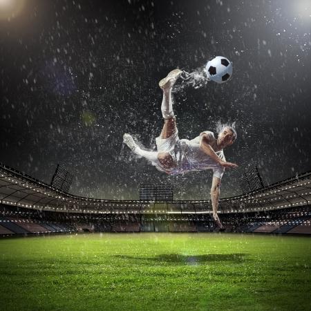 dribble: football player in white shirt striking the ball at the stadium under the rain Stock Photo