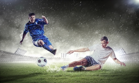 football players: two football players in jump to strike the ball at the stadium