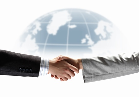 partnership power: business handshake against white background with globe image