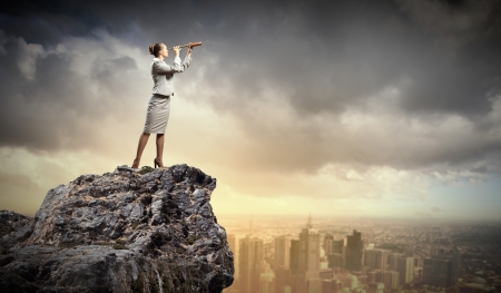 Image of businesswoman looking in telescope standing a top of rock Stock Photo - 18020991