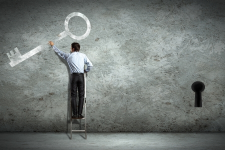 Image of businessman standing on ladder holding key photo