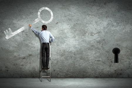 seeking solution: Image of businessman standing on ladder holding key