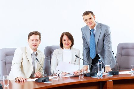 Image of three businesspeople sitting at table at conference Stock Photo - 18021072