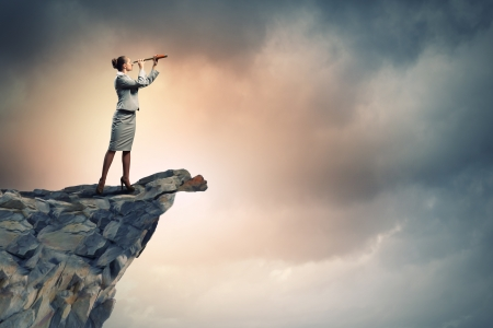 Image of businesswoman looking in telescope standing atop of rock Stock Photo - 18021083