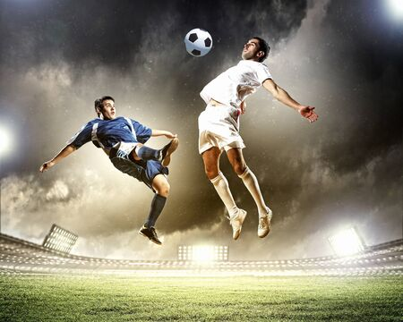 fast foot: two football players in jump to strike the ball at the stadium