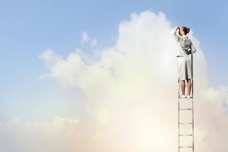 escaleras: Empresaria de pie en la escalera mirando en la distancia contra el fondo nublado Foto de archivo
