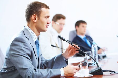 Boardroom meeting: Image of three businesspeople at table at conference