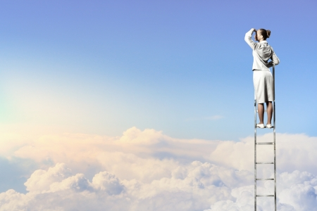 Businesswoman standing on ladder looking into distance against cloudy background photo