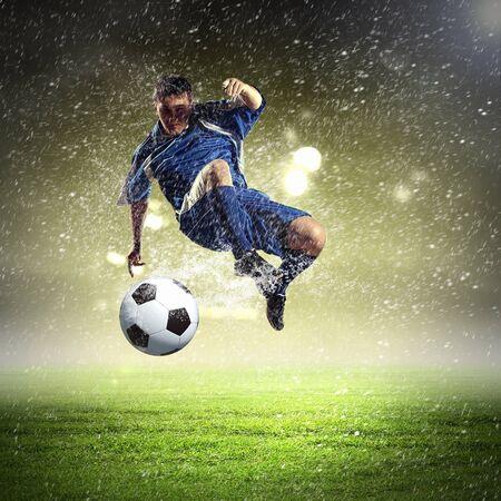 football player in blue shirt striking the ball aloft at the stadium under the rain
