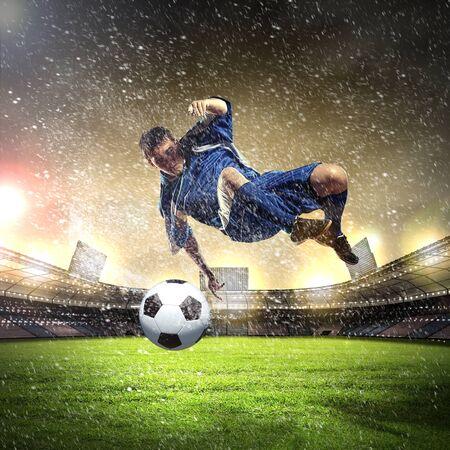 aloft: football player in blue shirt striking the ball aloft at the stadium under the rain