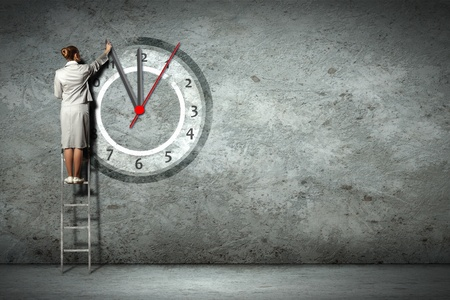 Businesswoman standing on ladder moving hands of clock photo