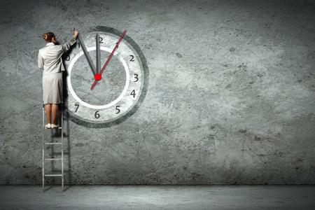 woman clock: Empresaria de pie en la escalera m�vil manos de reloj