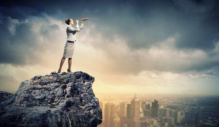Image of businesswoman looking in telescope standing atop of rock Stock Photo - 18020951
