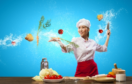 inair: Asian female cook with knife cutting fruits and vegetables in air