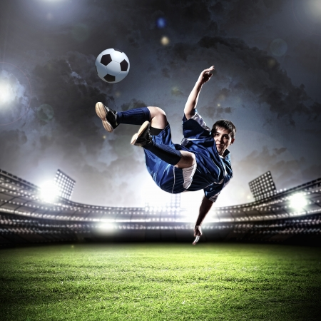 ball lightning: football player in blue shirt striking the ball aloft at the stadium
