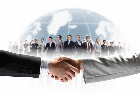 business handshake against white background and standing businesspeople photo