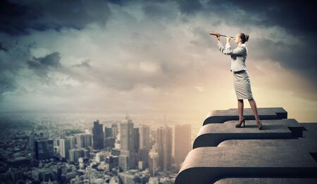 vision concept: Image of businesswoman looking in telescope standing a top of building