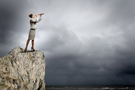 Image of businesswoman looking in telescope standing atop of rock Stock Photo - 18021040