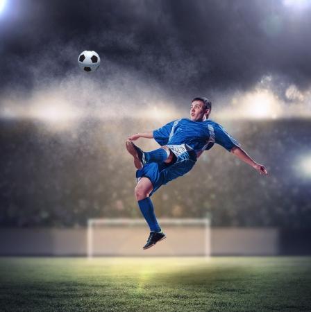 aloft: football player in blue shirt striking the ball aloft at the stadium