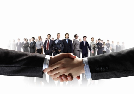 business handshake against white background and standing businesspeople Zdjęcie Seryjne