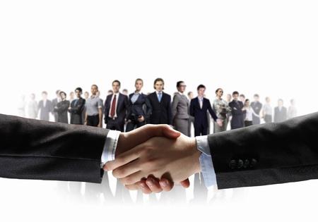 stimme: Business-Handshake vor wei�em Hintergrund und Stehen Gesch�ftsleute