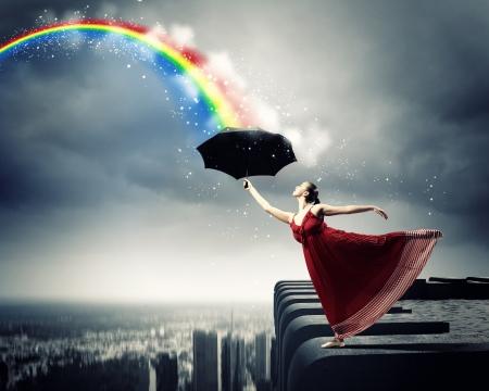 girl in rain: ballet dancer in flying satin dress with umbrella under the paint