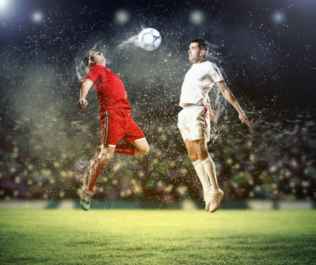 two football players in jump to strike the ball at the stadium Stock Photo - 18021149
