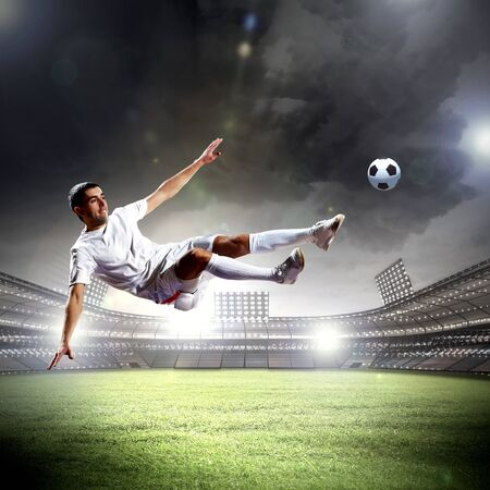 inair: football player in white shirt striking the ball at the stadium