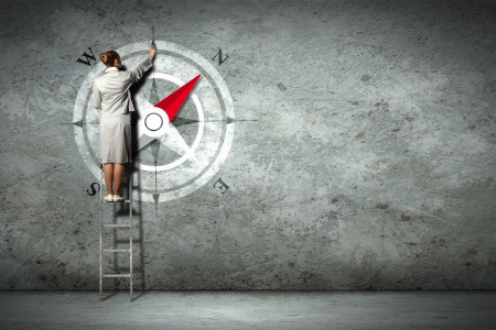 confidence: Businesswoman drawing compass with finger on wall standing on ladder