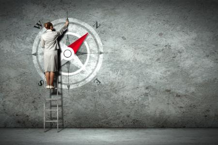 Femme d'affaires boussole de dessin avec le doigt sur le mur debout sur l'échelle