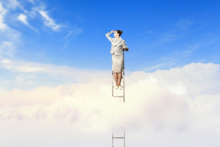goal oriented: Businesswoman standing on ladder looking into distance against cloudy background