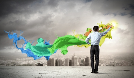 color mixing: young man standing with back painting splashes against city background Stock Photo