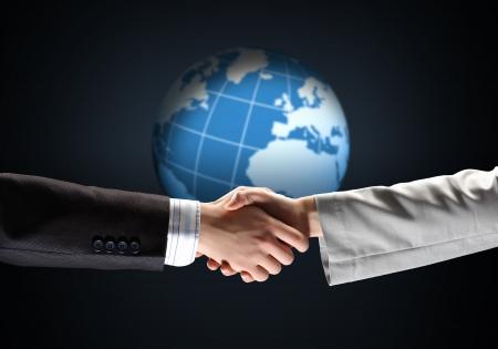 business handshake against black background with globe image photo