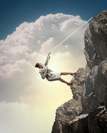 steep: businesswoman climbing steep mountain hanging on rope