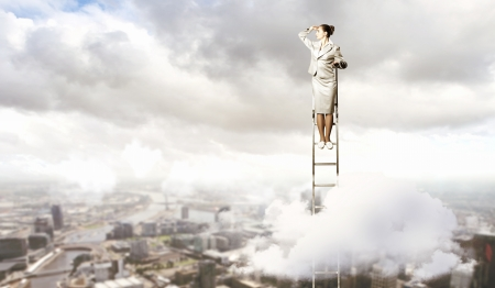 goal oriented: Businesswoman standing on ladder looking into distance against city background