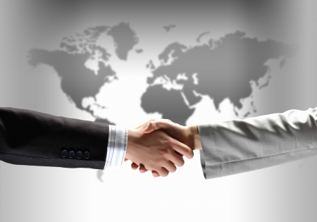 shakes hands: business handshake against black background with map image