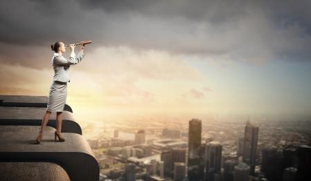 vision futuro: Imagen de la empresaria mirando en un telescopio de pie encima de la construcci�n de Foto de archivo