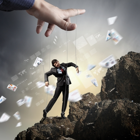 atop: Businessman marionette on ropes controlled by puppeteer standing atop of mountain