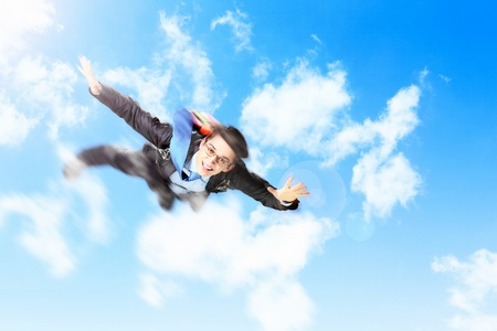 Conceptual image of young businessman flying with parachute on back photo