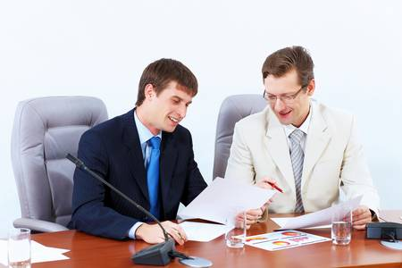 Image of two businessmen sitting at table at conference photo