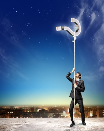 aloft: Image of businessman climbing rope attached to question sign aloft against city background Stock Photo
