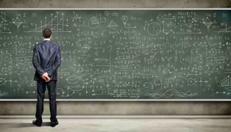 Business stehende Person gegen die Tafel mit einer Vielzahl von Daten auf sie geschrieben
