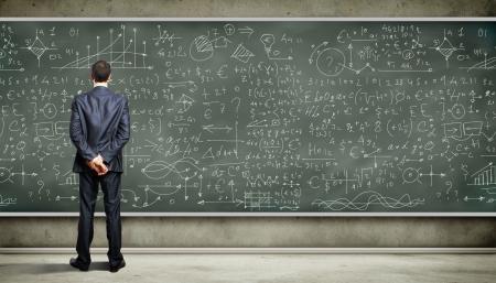 Personas de negocios de pie contra la pizarra con una gran cantidad de datos escrito en él
