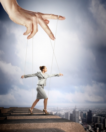tiedup: Businesswoman marionette on ropes controlled by puppeteer against city background