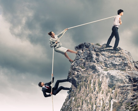 Image of three businesspeople pulling rope atop of mountain Stock Photo
