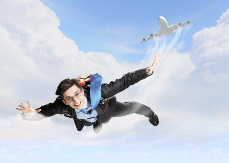 Conceptual image of young businessman flying with parachute on back Stock Photo - 18183008