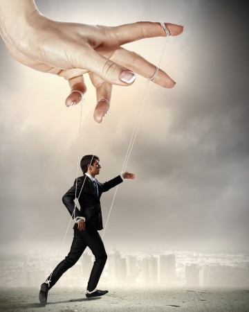 controlled: Businessman marionette on ropes controlled by puppeteer against city background