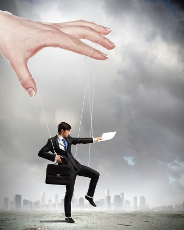 Businessman marionette on ropes controlled by puppeteer against city background Stock Photo - 18183104