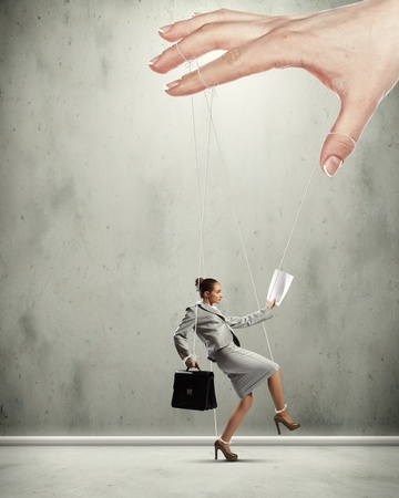 controlled: Businesswoman marionette on ropes controlled by puppeteer Stock Photo